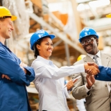 warehouse manager shaking hands with warehouse worker